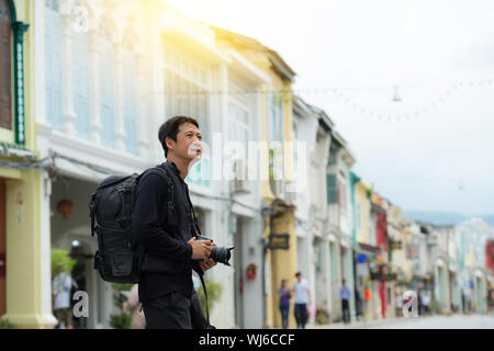 Tourist sightseeing old town ,traveling concept. Street photographer wandering on famous walking street in phuket  old town. - Stock Photo