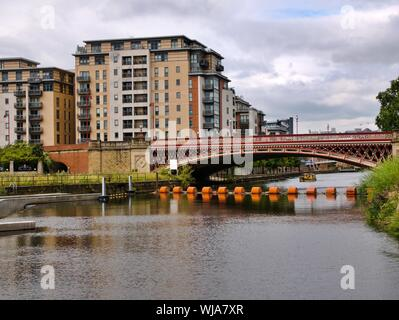 Red Bridge over the river Aire with orange boom with yellow river taxi in the background and flats in Leeds Yorkshire England - Stock Photo
