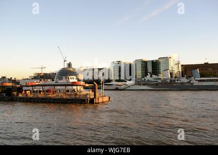 London/UK - August 31, 2014: Panoramic view to the embankment on the  Thames river, the cityscape and HMS Belfast at sunset. - Stock Photo