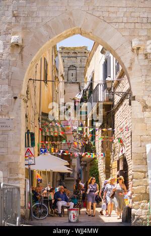 BARI, ITALY - JULY 11, 2018, View of a narrow street in Bari, Puglia, Italy, Bari vecchia, traditional open market shops with souvenir for tourists - Stock Photo