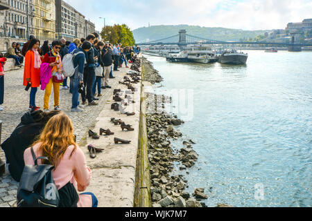 Tourists visit and take photos at The Shoes on the Danube Bank, a memorial in Budapest, Hungary with the Chain Bridge and boats in view - Stock Photo