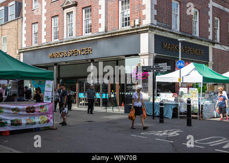 Winchester, Hampshire, UK The front of marks and Spencer shop in Winchester high street with shoppers walking past and market stalls in the street - Stock Photo