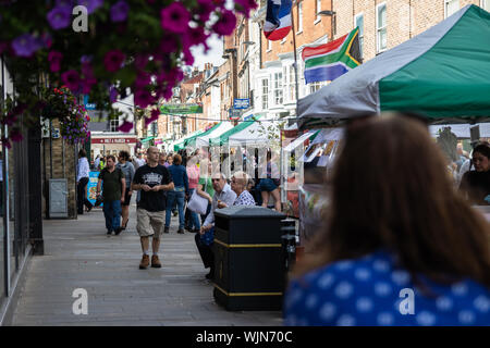 Winchester, Hampshire, UK A scene from a typical English City high street with shoppers walking through past market stalls and market trade - Stock Photo