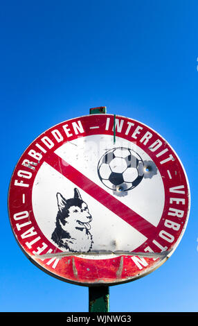 Sign prohibiting access to the dogs and to play football. They are well see two bullet holes. - Stock Photo