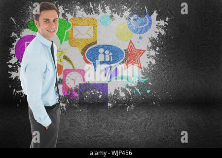 Happy businessman standing with hand in pocket against splash on wall revealing applications - Stock Photo
