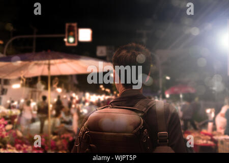Male tourist sightseeing flea market,traveling concept. Street photographer wandering on famous night walking street in chiengmai city, northern Thail - Stock Photo