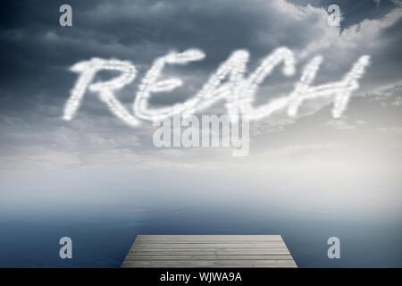 The word reach against cloudy sky over ocean - Stock Photo