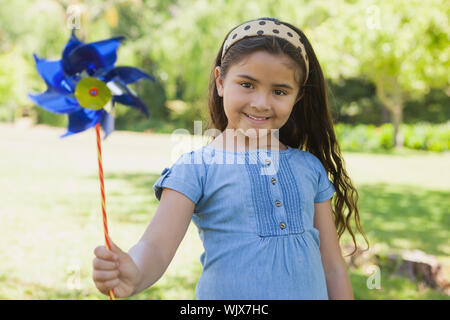 Portrait of cute little girl holding pinwheel at the park - Stock Photo
