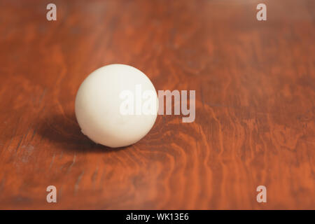 white ball on wooden desk in isolated background to fill - Stock Photo