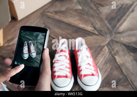 Online seller use mobile phone take a photo of product for upload to website online shop. - Stock Photo