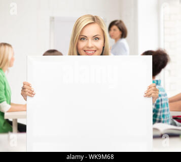 happy smiling woman with white blank board at school - Stock Photo