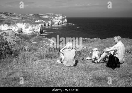 A couple and their dog resting on the clifftop at Flamborough Head, Yorkshire, UK - Stock Photo