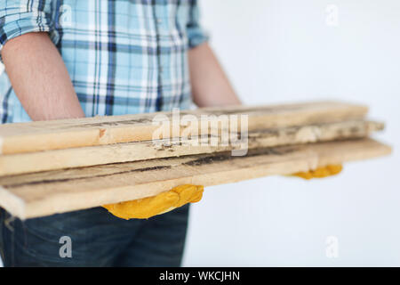 repair, building and home concept - close up of male in gloves carrying wooden boards - Stock Photo