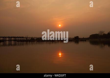 Sunset over the historic wooden U Bein Bridge near Mandalay in Burma - Stock Photo