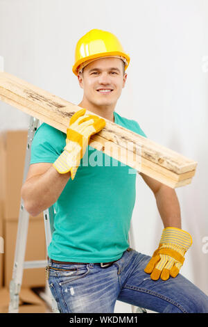 repair, construction and maintenance concept - smiling male manual worker in protective helmet carrying wooden boards - Stock Photo