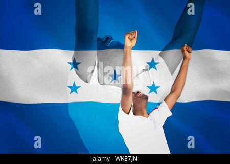 Excited handsome football fan cheering against digitally generated honduras national flag - Stock Photo