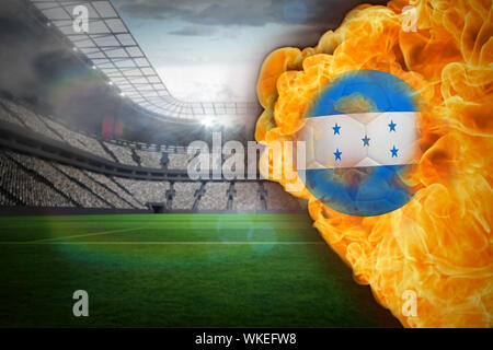 Composite image of fire surrounding honduras flag football against large football stadium with lights - Stock Photo