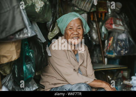 Phan Thiet, Vietnam - November 4, 2016: An unidentified vietnamese lady sitting at her shop in Phan Thiet, Vietnam. - Stock Photo