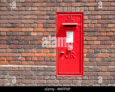 An old GR red post box or mail box set into a brick wall in Cambridge UK - Stock Photo