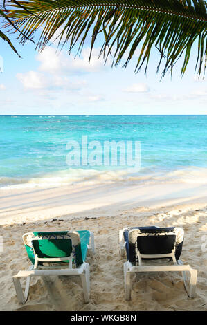 Two beach chairs under a palm tree on the ocean shore in tropical resort - Stock Photo