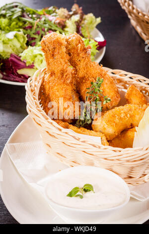 Crisp crunchy golden chicken legs and wings deep fried in bread crumbs and served with a bowl of dip in a wicker basket for a delicious appetizer - Stock Photo