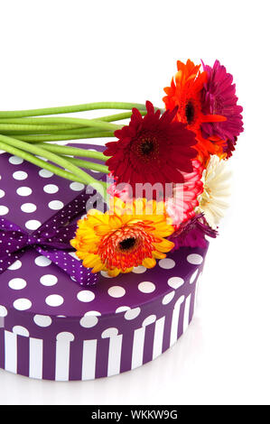Purple present with speckles and stripes and flowers isolated over white - Stock Photo