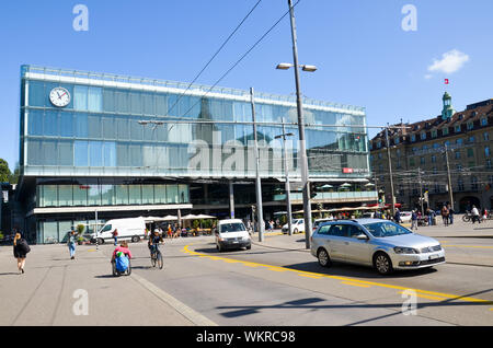 Bern, Switzerland - August 14 2019: Building of the main train station in Swiss capital photographed from outside with people on the street and cars on the adjacent road. - Stock Photo