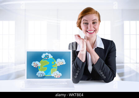 Excited redhead businesswoman sitting at desk with laptop showing graphic - Stock Photo