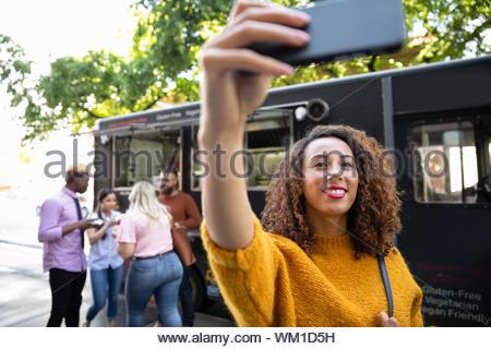 Smiling woman taking selfie outside food truck - Stock Photo