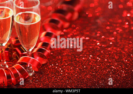 Glasses with Champagne and gifts on red glitters background - Stock Photo