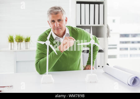 Casual businessman looking at model wind turbines in his office - Stock Photo