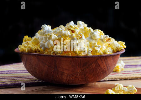 Homemade theater popcorn with butter in wooden bowl for movie night - Stock Photo
