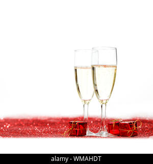 Glasses with Champagne and gifts on red glitters isolated on white background - Stock Photo