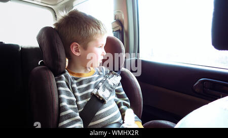 Little cute boy in a car seat looks out the window. Pure emotions over child face. - Stock Photo
