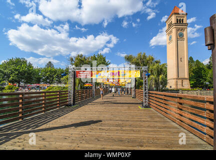 Visitors cross the bridge over the Spokane River near the clock tower at the annual Pig out in the Park festival in downtown Spokane Washington - Stock Photo
