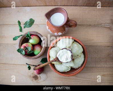Tasty fresh milk is one of the main sources of nutrition. Dumplings and apples rustic food. On the general background. copyspace - Stock Photo