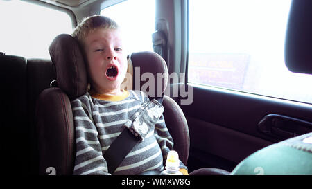 Little cute boy in a car seat looks out the window and yawns. Pure emotions over child face. - Stock Photo