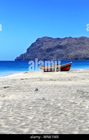 Fishing boats on the beach, São Pedro, Island São Vicente, Cape Verde, Cabo Verde, Africa.  Farol de Dona Amélia in the background. - Stock Photo