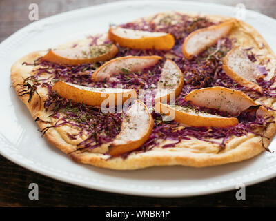 Traditional German flammkuchen (flatbread) with red cabbage and pears. - Stock Photo