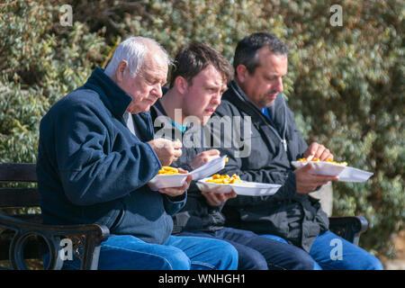 Three men eating fish and chip supper at Lytham St Annes, UK - Stock Photo
