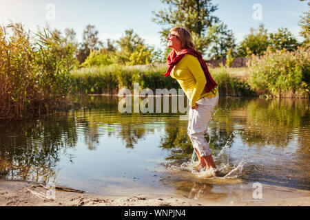 Middle-aged woman jumping on river bank on autumn day. Happy senior lady having fun walking in the forest. Feeling energetic and free - Stock Photo