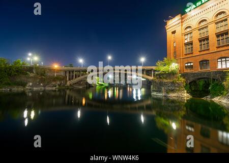 Evening in downtown Spokane Washington on the Spokane River near the historic utility building in Riverfront Park - Stock Photo