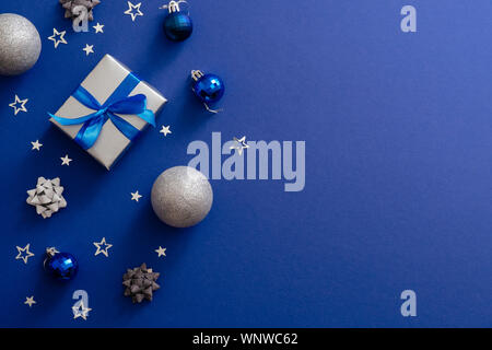 Christmas silver gift box with bow ribbon, baubles, decorations, confetti on magic dark blue background with copy space. Vintage Xmas greeting card mo - Stock Photo