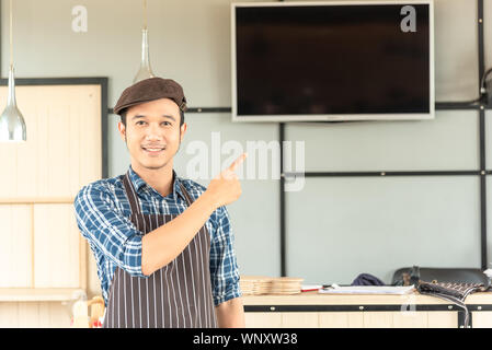 The young asian man who is wearing an apron confidently smile and point to something above him to the blank monitor behind him at a workplace in the m - Stock Photo