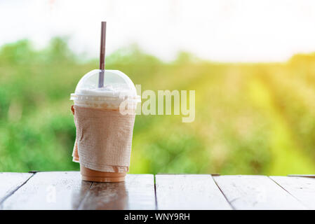 A take away glass of iced cappuccino coffee  is on the wooden table with background is blurred green nature outdoor among of sunlight in the summer mo - Stock Photo
