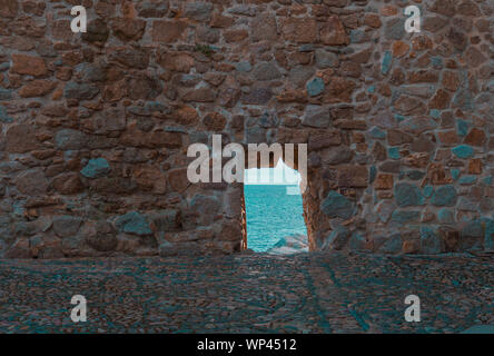 Hole in the medieval stone wall of Tossa de Mar, Spain. - Stock Photo