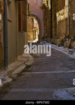 Narrow alley with decorated tunnel, in Pyrgi  medieval village, Chios island, Greece. - Stock Photo