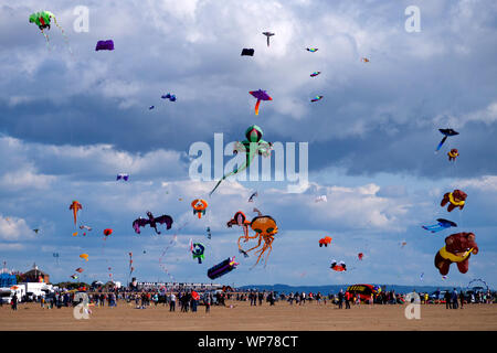 Sunshine and a good strong wind bring colour to the skies at the St. Annes International Kite Festival in Lancashire, England. - Stock Photo