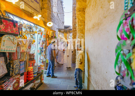 DOHA QATAR - JULY 11 2019; Focus on Arabic man in customary white robes in lane among market vendors and products and ambience of Souq Waqif - Stock Photo