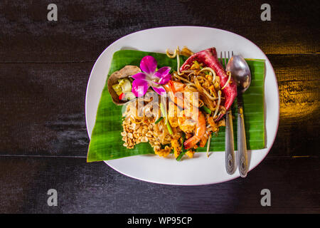 Thai Fried Noodles 'Pad Thai' with shrimp and vegetables on the white ceramic dish decorated with orchid put on dark wooden table. Select focus. - Stock Photo